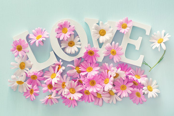 "The word ""love"" and daisies flowers on a blue background for a Valentine's Day."