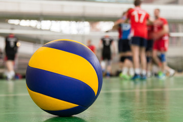 Yellow-blue volleyball on the floor in the gym, team of athletes is a bunch