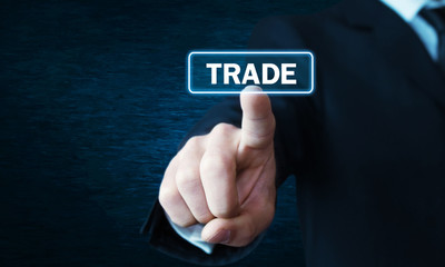 Man hand clicking Trade button on screen.