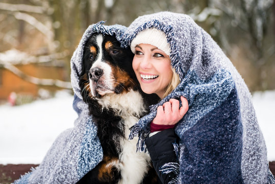 Woman and her dog getting warm on cold winter day under a blanket snuggling