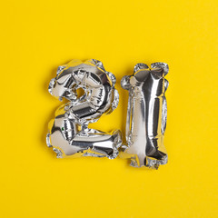 Silver foil number 21 celebration balloon on a bright yellow background