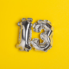Silver foil number 13 celebration balloon on a bright yellow background