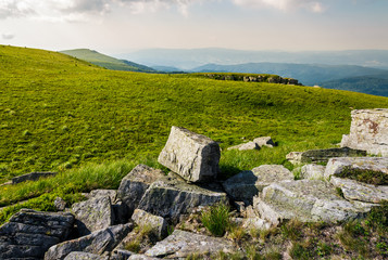 rocks on grassy meadow on top of a hill. beautiful summer scenery in mountains
