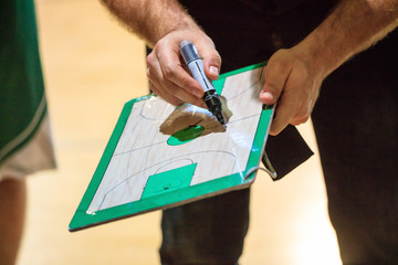 Basketball coach holds a clipboard and with a marker explain the tactic of the game to a player.