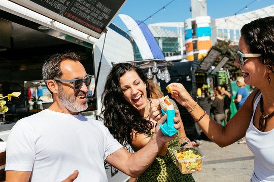 People eating snacks at food truck