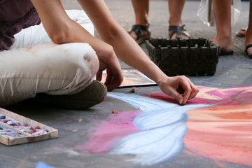 Summer. Italy. Florence. The artist paints a picture with chalk on the asphalt