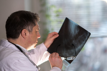 Back turned concentrated radiologist reading X-ray images