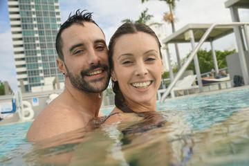 Cheerful couple enjoying bath in resort swimming pool