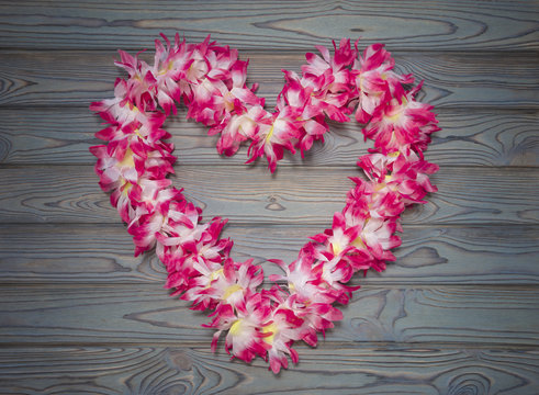 Hawaiian wreath of flowers in the shape of heart on a blue wooden background. day of lovers. Denis the saint valentine, love