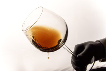 Photo of male hand with glass of a brown wine.