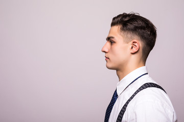 Side view portrait of confident man with beautiful hairstyle in white shirt looking on copy space isolated on white