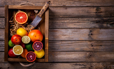 Different Citrus Fruit in a wooden box .Mixed Colorful Tropical Background.Food or Healthy diet concept.Vegetarian.Copy space for Text. selective focus.Toned image.Vintage style.