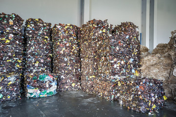 Stock of plastic brown pressed bales at the modern waste hazardous processing plant. Separate garbage collection. Recycling sorting and storage of waste for further disposal.