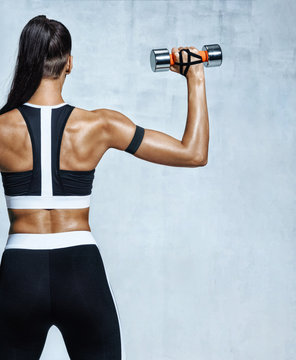 Rear view of woman exercising with dumbbell