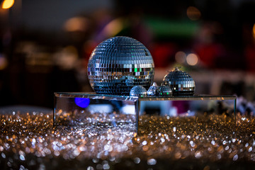 Mirrored disco balls on top of mirrored platform surrounded by glitter and jewels as centerpiece on table at party.