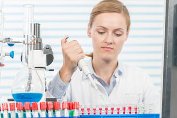 Experiments in the chemical laboratory, Female researcher using her test tube in a laboratory