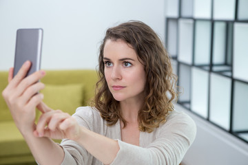 Serious Young Woman Taking Selfie at Home