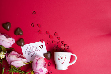 Delicious chocolate candies and flowers on red background