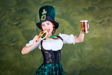 A girl in a St. Patrick costume with a mug of beer is smiling on a green background.