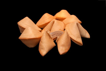 A pile of fortune cookies on black background