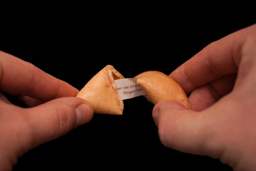 two hands cracking a fortune cookie