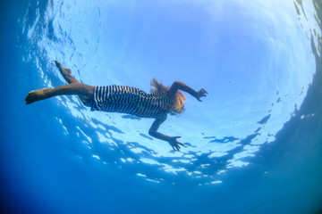little blonde girl in sea water underwater