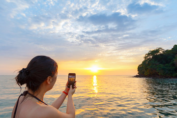 young beautiful woman tourist taking picture of sunset on a sunset cuise in cambodia, sihanoukville with phone