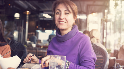 Middle age woman in restaurant having a meal
