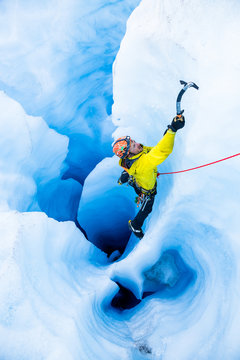 Ice climber on rope climbing out of moulin with multiple vertical tunnels