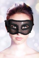 Junge hübsche Frau mit Maske blickt cool