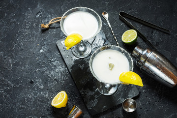 Alcohol cocktail margarita on a black stone table, with lemon. lime and shaker
