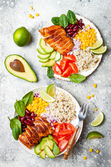 Homemade Mexican chicken burrito bowl with rice, beans, corn, tomato, avocado, spinach. Taco salad lunch bowl