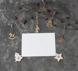 on a gray background birch branches and Christmas decor: cones, Christmas toys, a sheet of paper and red currant paper