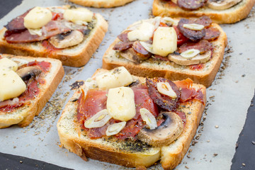 Toasts with ham, cheese and mushrooms on a white background