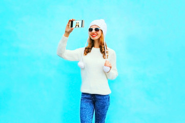 smiling woman takes a picture self portrait in white knitted sweater, hat on a smartphone on blue background