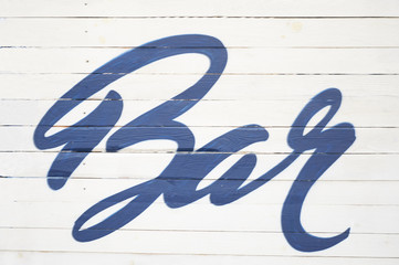 """The inscription """"Bar"""" on the fence. Blue inscription in a beautiful font. The atmosphere of summer, relaxation, rest. Place for parties and alcohol."""