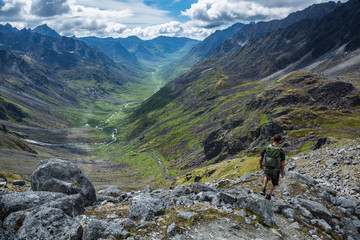 Hiker descending steep rocky trail above glacial valley in Alaska Wall mural