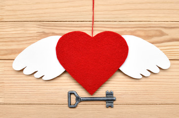 Red heart - a symbol of love on a wooden background.