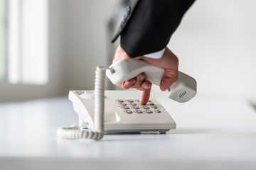 Male hand dialing a telephone number in order to make a phone call