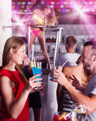 Female and male clubbing with cocktail in the club on party