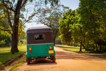 Green tuk tuk on the sand road, Sri Lanka