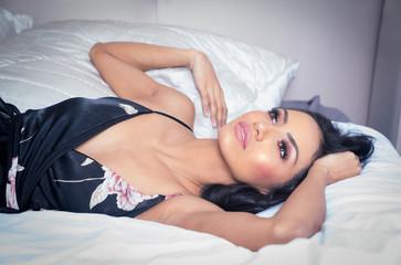 Beautiful exotic woman wearing dress on bed