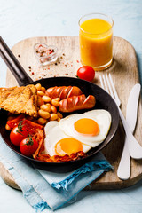 English Breakfast in a skillet. Eggs in the Heart shape. Valentine's Day. Festive Food on the Blue Background.Sausages, Bacon, Beans, Тоустс,Orange juice and Coffee