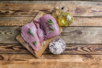 Fillet of a turkey on a chopping board. Spices, olive oil, fragrant herbs. Wooden rustic background