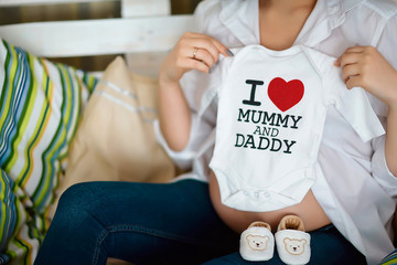 Small shoes and a sweater with text for the unborn baby in the belly of pregnant woman, pregnant woman holding small baby shoes and a sweater with text relaxing at home in bedroom