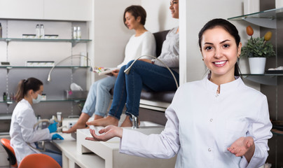 Young  nail salon master inviting clients to procedure