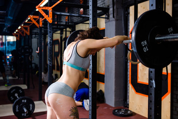 Crossfit and sport theme. A beautiful sexy girl with a bare booty in a bikini stands tired near the bar and rests after a hard training session. Deadlift and training of leg and back muscles