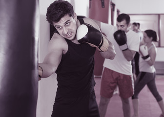 strong sportsman in the boxing hall practicing boxing punches with boxing bag