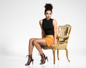 Fashion Model Posing in a Chair wearing a Black Tank Top and Yellow Skirt