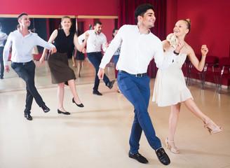 Young people practicing vigorous jive movements